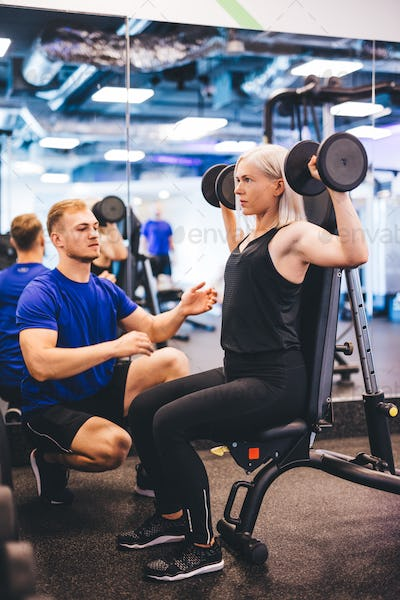 Woman lifting weights, exercising with personal trainer.