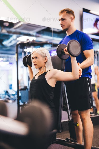 Woman at the gym exercising with personal trainer.