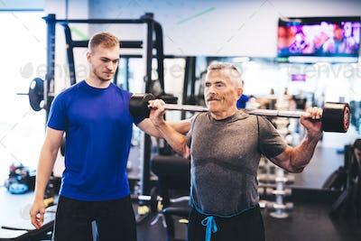 Older man assisting senior man at the gym.