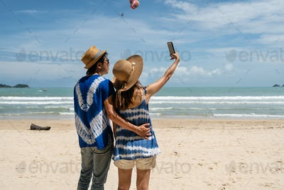 Loving couple traveler making selfie on the tropical beach
