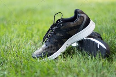 Pair of man sport shoes on green field
