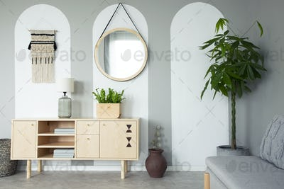 Round mirror hanging on the wall in real photo of grey living ro