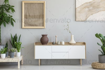 Real photo of a botanic living room interior with burlap artwork