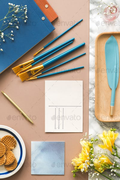 Top view on paint brushes and postcard on desk with yellow flowe