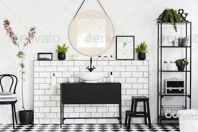 Mirror above black washbasin in white bathroom interior with cha