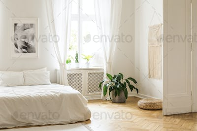 Beige macrame and a poster on the white walls of a bright, minim