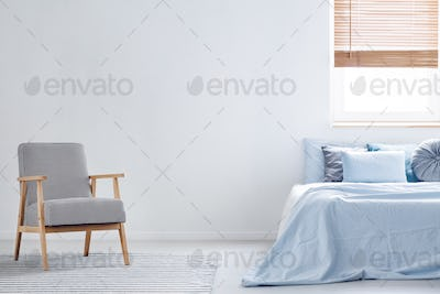 Patterned armchair on carpet in minimal bedroom interior with bl