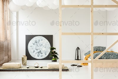 Pillows on the floor and moon poster in bedroom interior with la