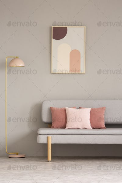 Pink lamp next to grey couch with cushions in living room interi