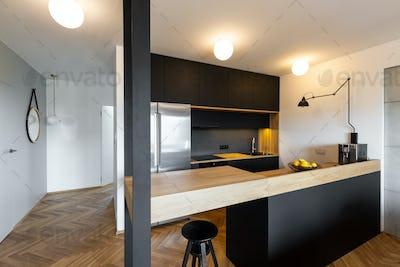 Stool under beige countertop in black kitchen interior with ligh