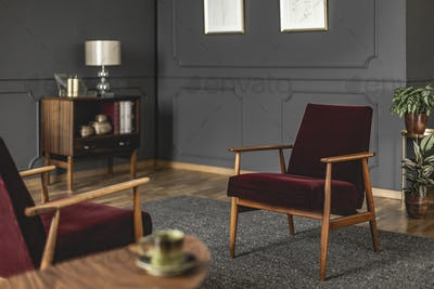 Burgundy armchair placed on dark carpet in grey living room inte