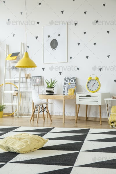 Yellow pillow on geometric carpet in kid's room interior with wh