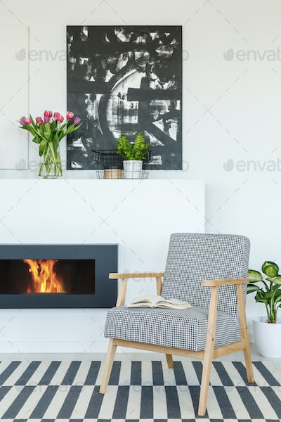 Painting above fireplace in modern living room interior with pat