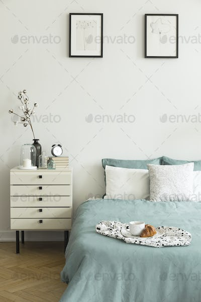Real photo of white bedroom interior with breakfast placed on be