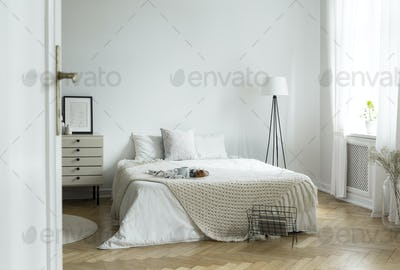 White bedroom interior in real photo with king-size bed with kni