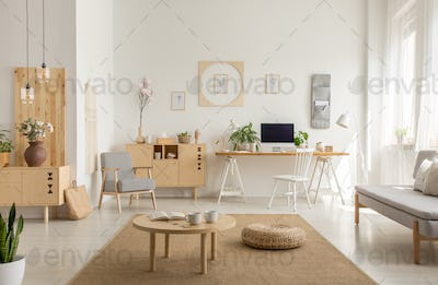 Wooden table and pouf on carpet in white living room interior wi