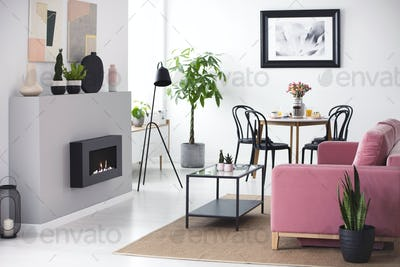 Real photo of bright living room interior with posters, dining t