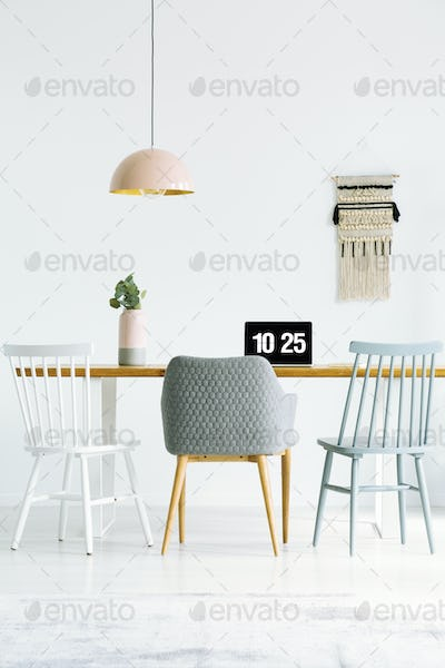 Chairs at wooden table with laptop and plant in bright workspace