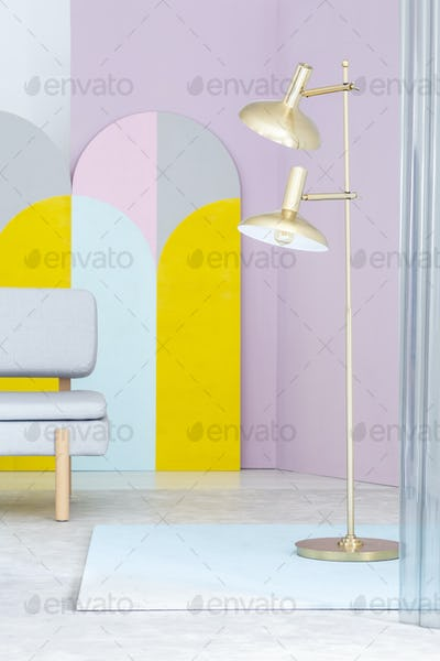 Real photo of a golden floor lamp and a gray sofa in colorful li