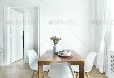 Dining table with fresh flowers and breakfast tray with coffee c