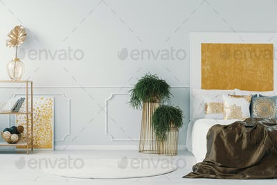 Real photo of a glamor bedroom interior with plants in golden po