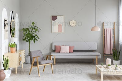 Sofa with pastel pink cushions in real photo of grey living room