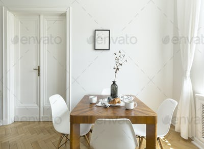 White chairs at wooden table in minimal dining room interior wit