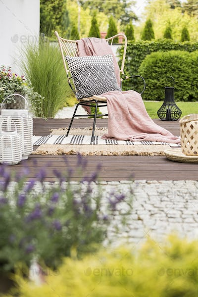 Cozy pillow with pattern and a pink blanket on a garden chair ou
