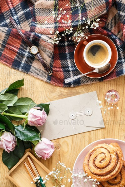 High angle on pink roses on wooden desk with cup of coffee and b