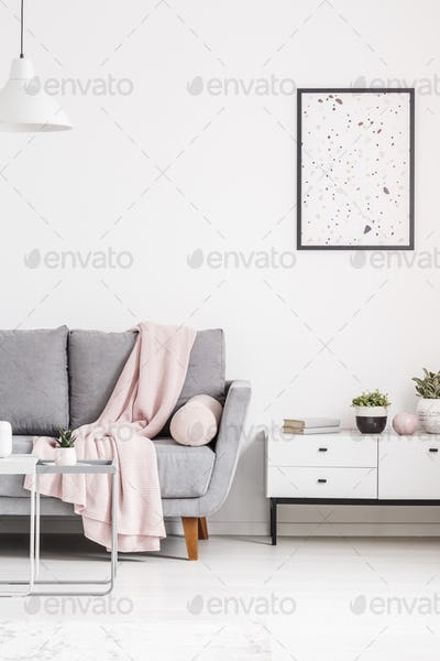 Modern poster on a white wall, grey sofa with blanket and cabine