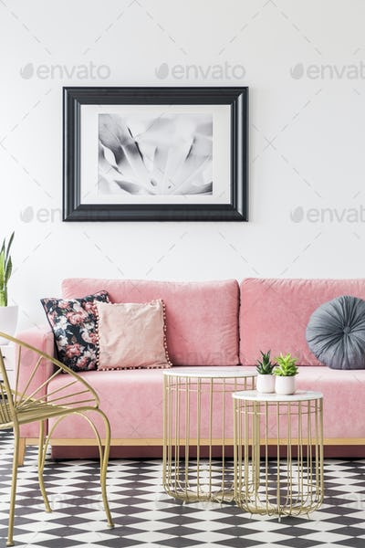 Pink sofa decorated with pillows, poster on the wall and golden