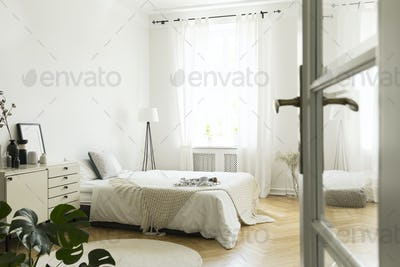 Knit blanket on bed in white bedroom interior with lamp next to