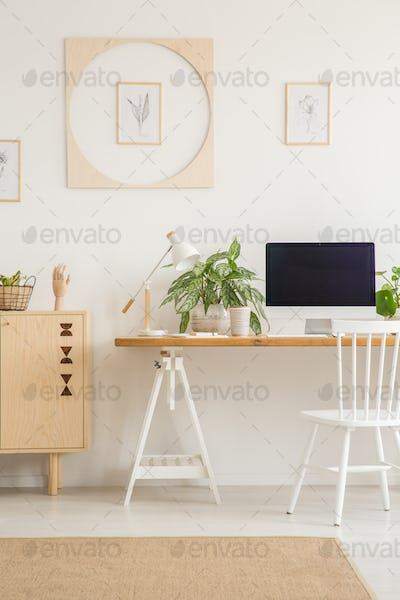 White chair at desk with desktop computer in workspace interior
