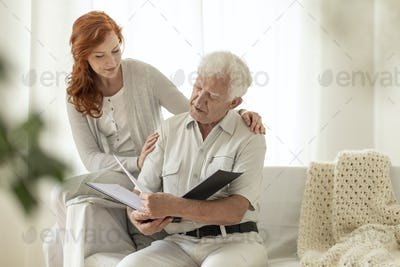 Senior man watching photo album during visit of granddaughter at