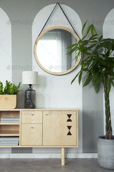 Round mirror above wooden cabinet with lamp in minimal flat inte