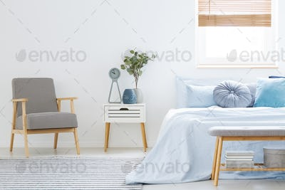 Plant on white cabinet between patterned armchair and blue bed i