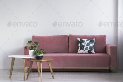 Pink sofa with a patterned pillow and two coffee tables with pla