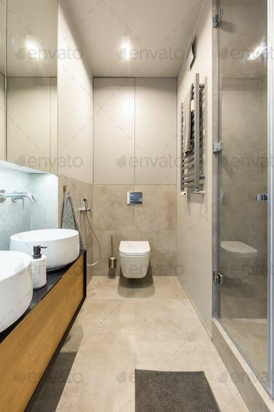 White toilet under light in modern beige bathroom interior with