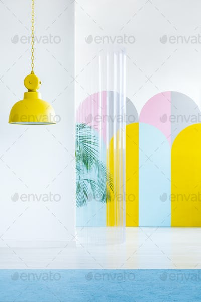 Yellow lamp, colorful wallpaper and plastic tube in a room inter