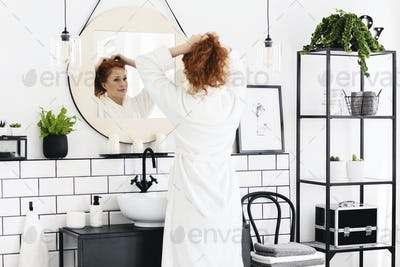 Woman in front of mirror in minimal bathroom interior with poste