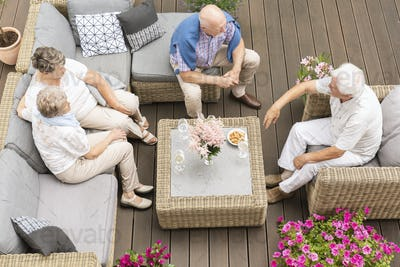 Top view on meeting of active elderly people on terrace with flo
