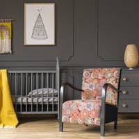 Patterned armchair next to kid's bed with yellow blanket in bedr