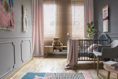 Drapes and blinds on windows in child's bedroom interior with pi