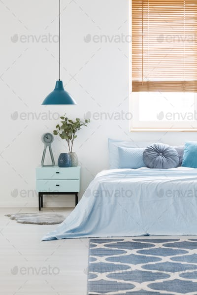 White bedroom interior with blue bedding on double bed, navy lam