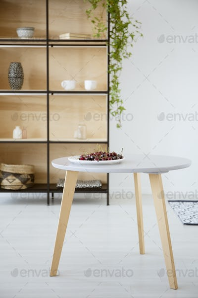Real photo of a plate of cherries on a round, wooden table in br