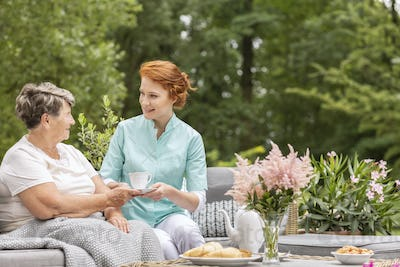 Happy nurse giving tea to elderly woman while eating breakfast o