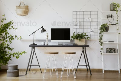 Stools at desk with lamp and desktop computer in freelancer's in
