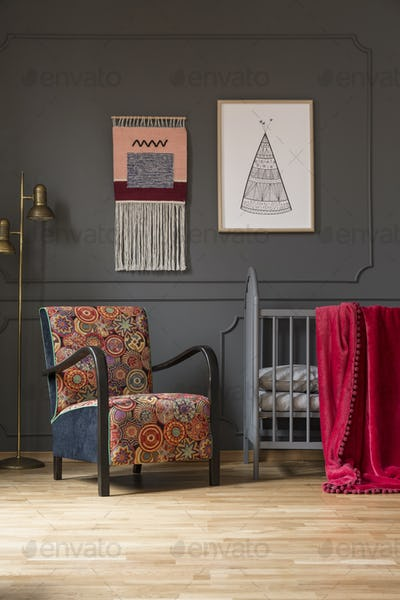 Patterned floral armchair next to baby's bed in bedroom interior