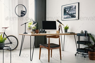 Chair at desk with desktop computer in home office interior with