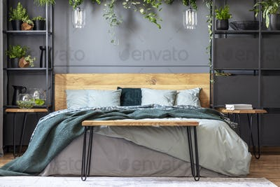 Hairpin bench standing by the king-size bed with many cushions a